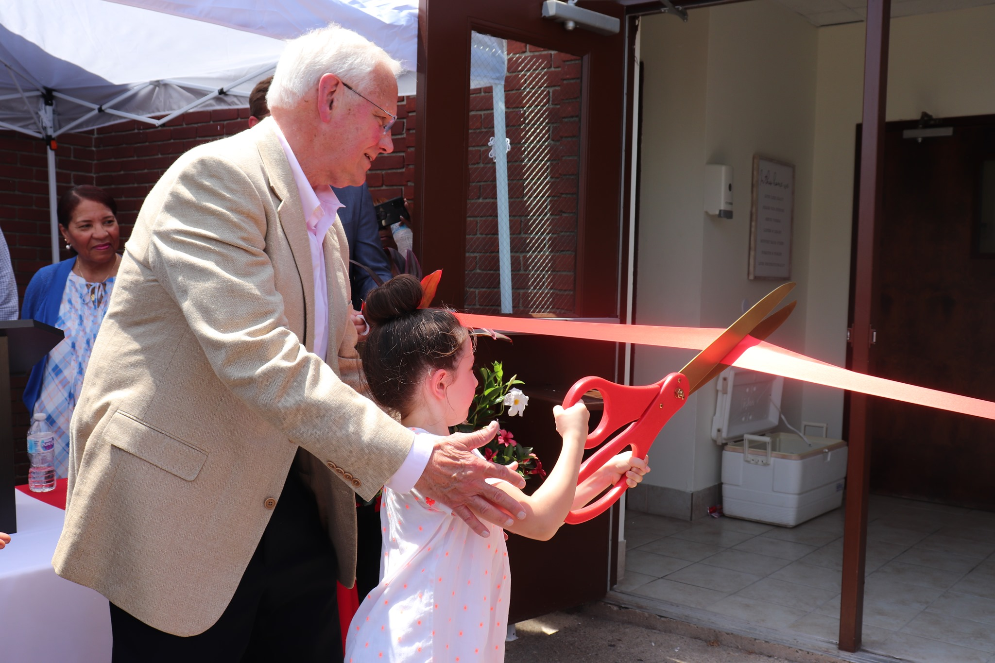 A man and child cutting the ribbon at the grand opening of Lucy Baney Reunification Center